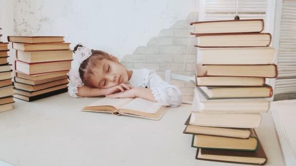Malá holka ve školní uniformě, usnula při čtení knihy.