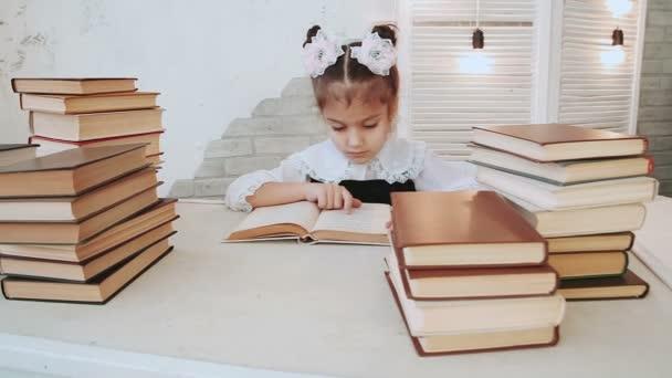 Portrét mladé školačky, který seděl u stolu s knihou.