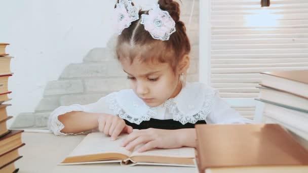 Dítě sedí u stolu vede prst přes stránkové knihy v popředí Stoh knih.