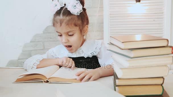 Školačka sedí u stolu a čtení knihy, při čtení to zívá.