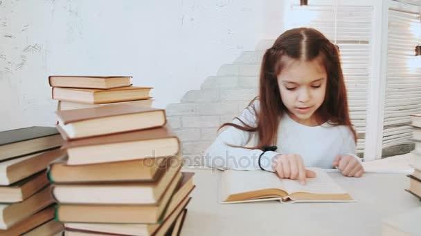 Dívka s krásné černé vlasy sedí u stolu a čte v literatuře.