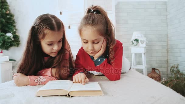 Two children sitting in a white room, reading a book in the background green tree.