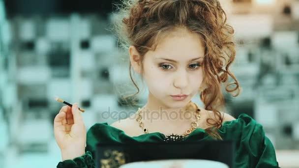 Dívka použití make-up před zrcadlo doma.