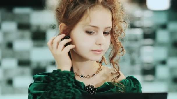 Obrázek hezká holčička, podívejte se do zrcadla a uvedení na náušnice