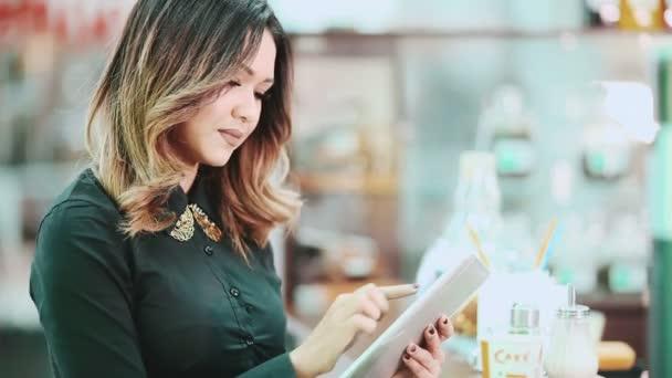 Giovane donna felice casuale mezzo della sua compressa in un caf.