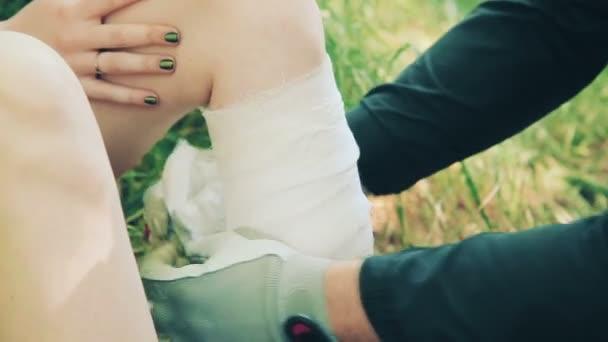 Mladý muž zabalení nohy dívky s detailním obvaz