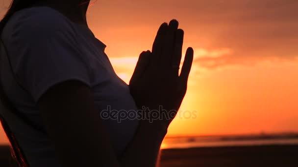 Silhouette einer jungen Frau beim Sonnenuntergang