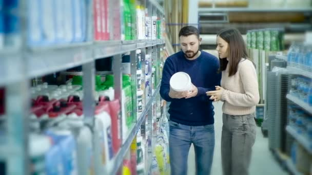 Married couple in a construction supermarket choose paint for repairs.