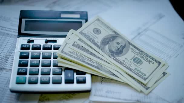 Vedle kalkulačky, několik bankovek amerických dolarů spadlo na účetní dokumenty.