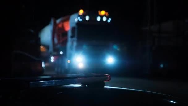 Těžký náklaďák na pozadí policejního blikajícího světla.