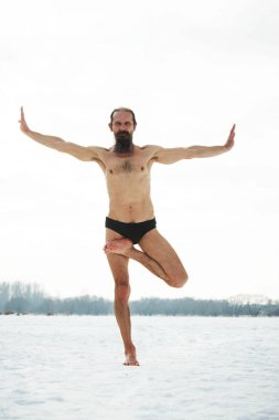 A middle-aged man is engaged in yoga on a frozen river. Vrishasa