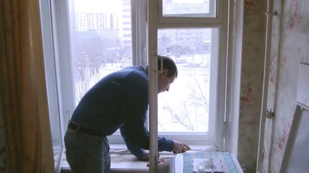 Člověk opraví dřevěných oken. Nahradit střepy na okno