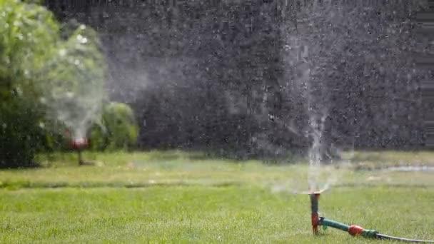 Dvě zahradní sprinklery zavlažování trávníku