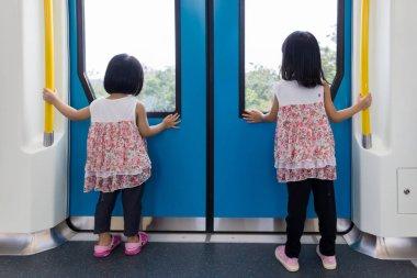 Asian Chinese little girl inside train looking beside the window