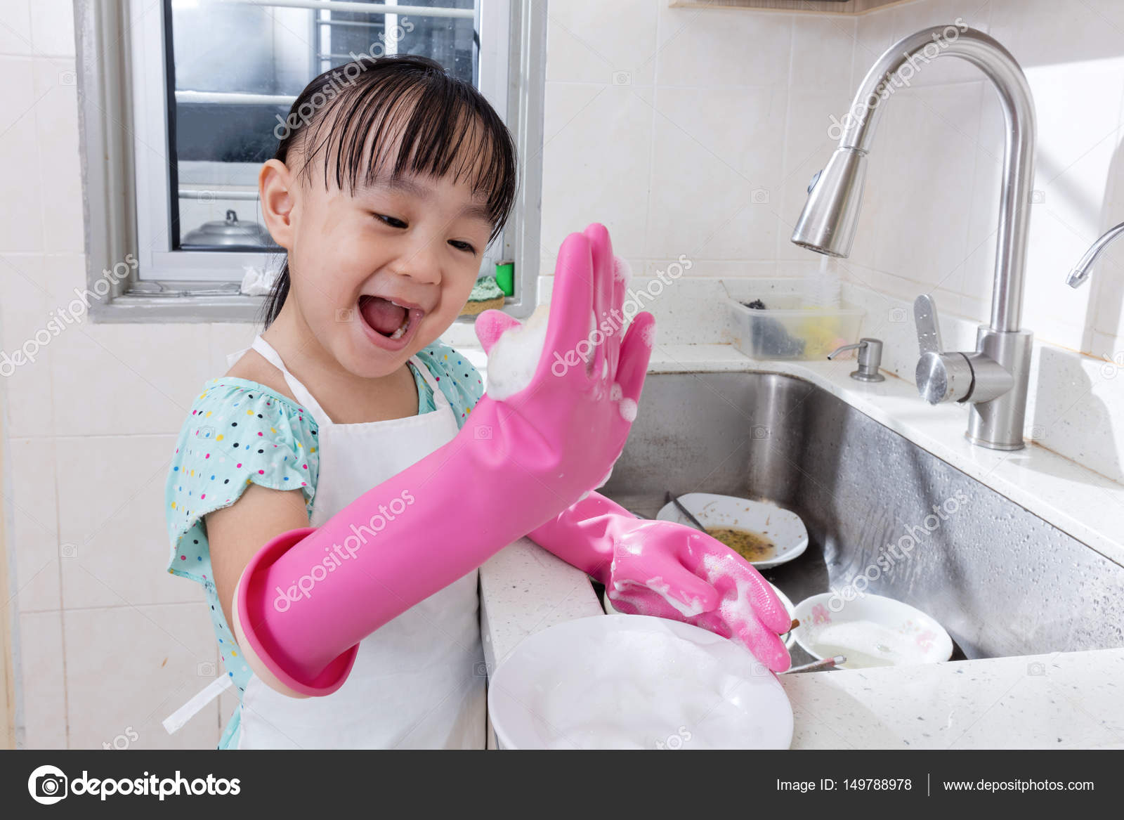 Mädchen in Gummihandschuhen putzt Badezimmer mit Tuch und
