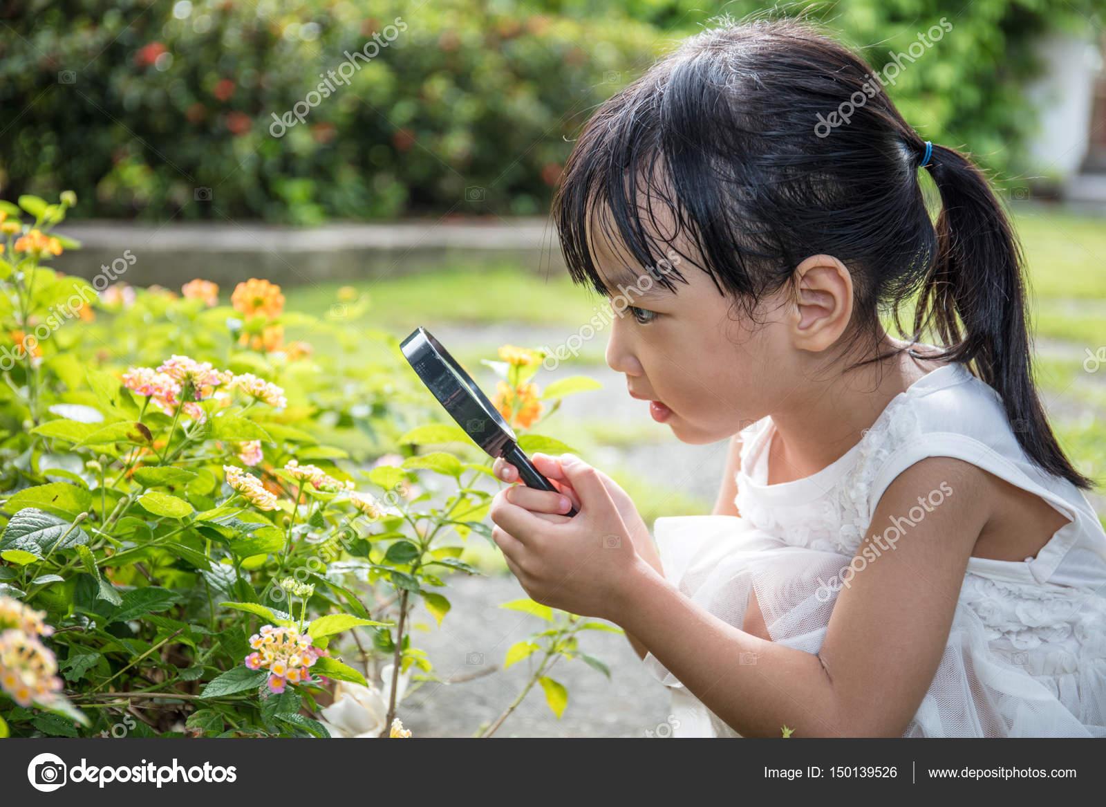 d8321a0af3a6 Asijská Čínská holčička při pohledu na květinu přes zvětšovací sklo ve  venkovní zahradě — Fotografie od ...