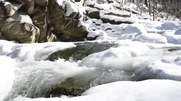 Zimní řeka s vodopádem a spoutaného pobřeží, rychlé proudy voda z tajícího ledu