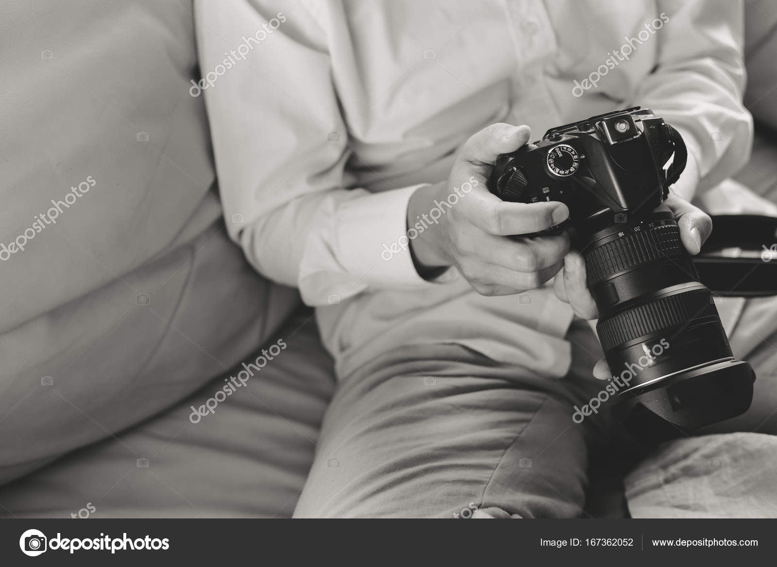 Black and white closeup picture dslr camera in hands of a person sitting on couch top side view mock up background photo by