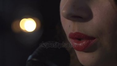 Woman singing into microphone close up