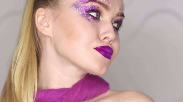 krásy makeup. fialové make-up a barevné světlé hřebíky. krásná dívka detailní portrét
