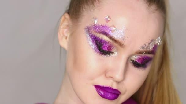 Beauty Make-up. Purpurfarbenes Make-up und bunte, helle Nägel. schöne Mädchen Nahaufnahme Porträt