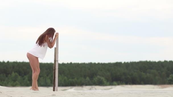 Sexy štíhlá žena svůdně zvedá nohy na dřevěné podpěrné