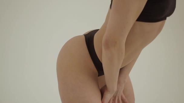 Dokonalé tělo mladé ženy na bílém pozadí v sexy prádle
