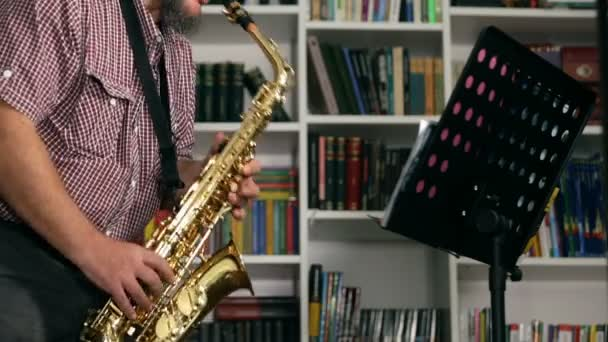 Musician composing jazz saxophone music, books on background