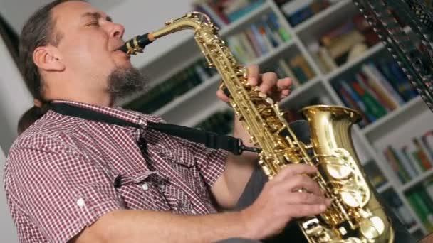 Vidám zenész játszik szaxofon, jazz, könyvespolcok a háttérben