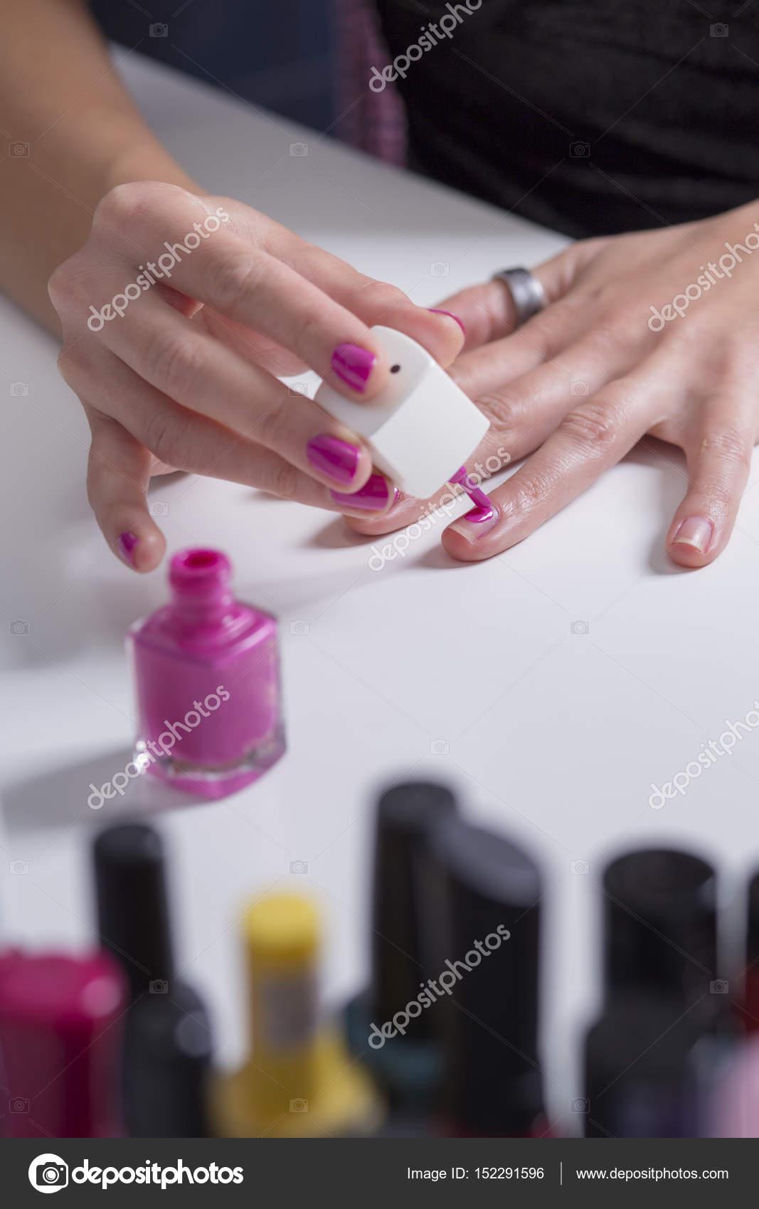 Mädchen malt ihre Nägel mit rosa Nagellack — Stockfoto © darezare ...
