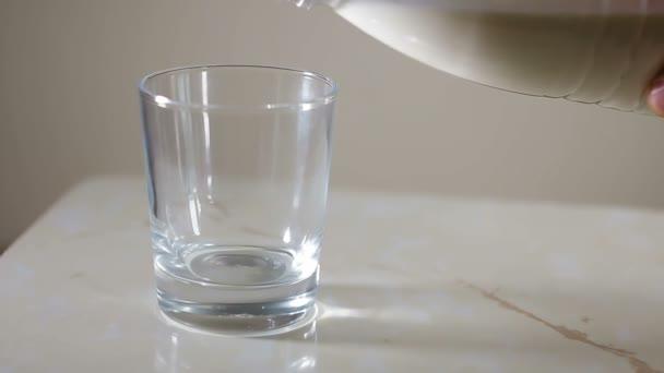 Čerstvé mléko se nalije do sklenice. Váleček neobsahuje reklamní text a emblémy. Transparentní hrnek a láhev bílé barvy jsou používány. Nejasné pozadí s studinny světlem