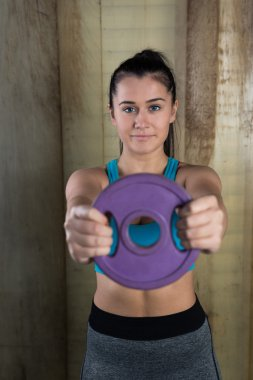 Sportive woman holding barbell plate