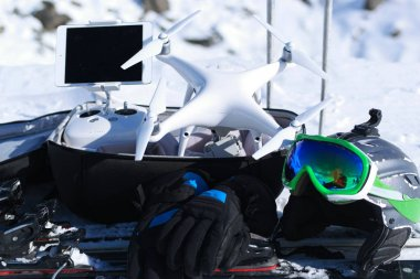 drone quad copter with high resolution digital camera and its remote control pad with smartphone on snow with equipment for skiing