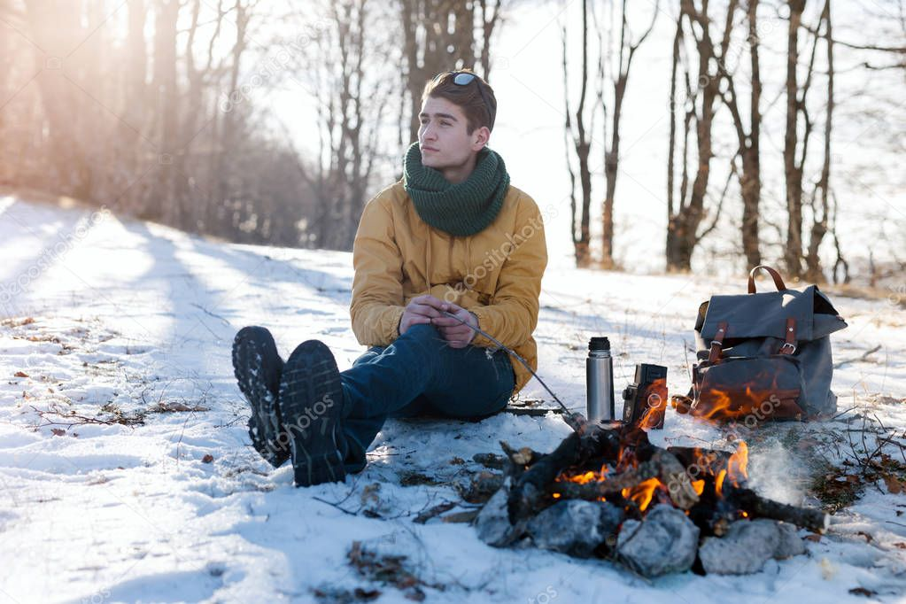 Man on mountain relaxing at campfire