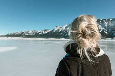 rear view of woman looking at mountain and frozen lake
