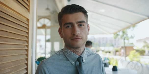 mladý pohledný podnikatel v obleku nosit brýle ve venkovní kavárně