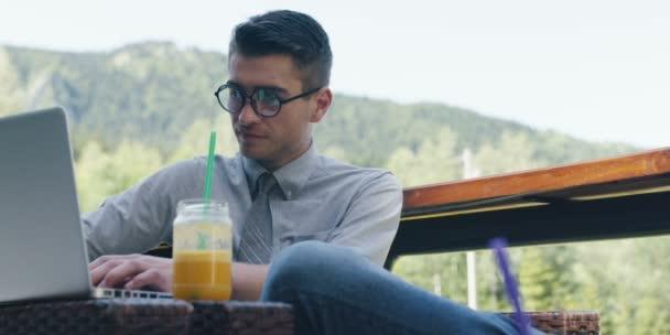 pohledný podnikatel v brýlích s moderní notebook ve venkovní kavárně