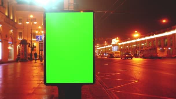 egy óriásplakát, egy zöld képernyő egy utcán