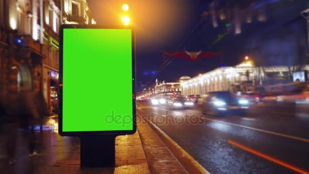 a Billboard With a Green Screen on a Evening Streets