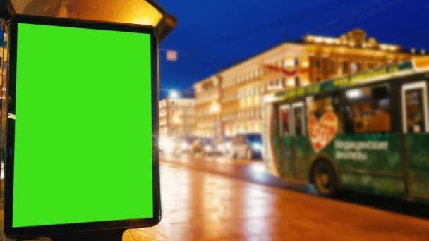 egy óriásplakát, egy zöld képernyő egy esti utcán