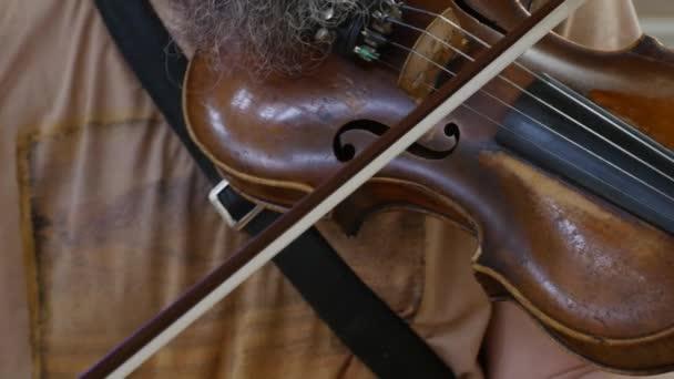 Hudebník hraje na housle. Detailní záběr