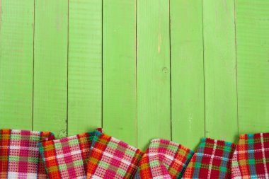 Red checkered tablecloth on a green wooden table with copy space for your text. Top view