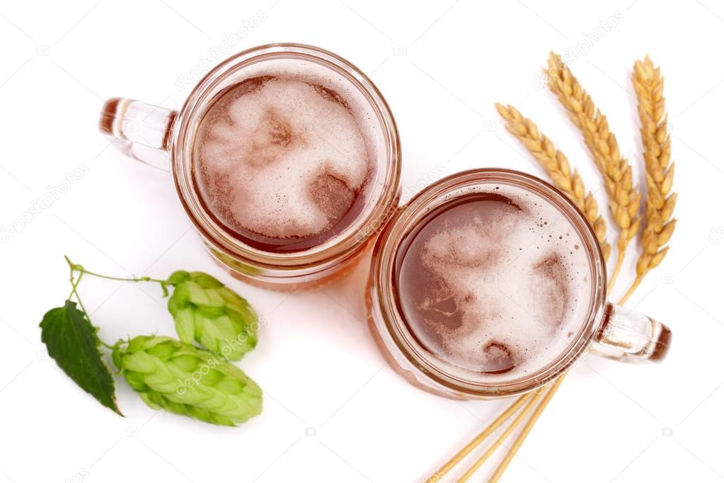 glass of foamy beer with hop cones and wheat isolated on white background. Top view