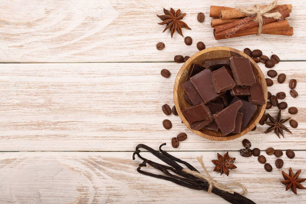 chocolate, vanilla sticks, cinnamon, coffee beans on white wooden background with copy space for your text. Top view