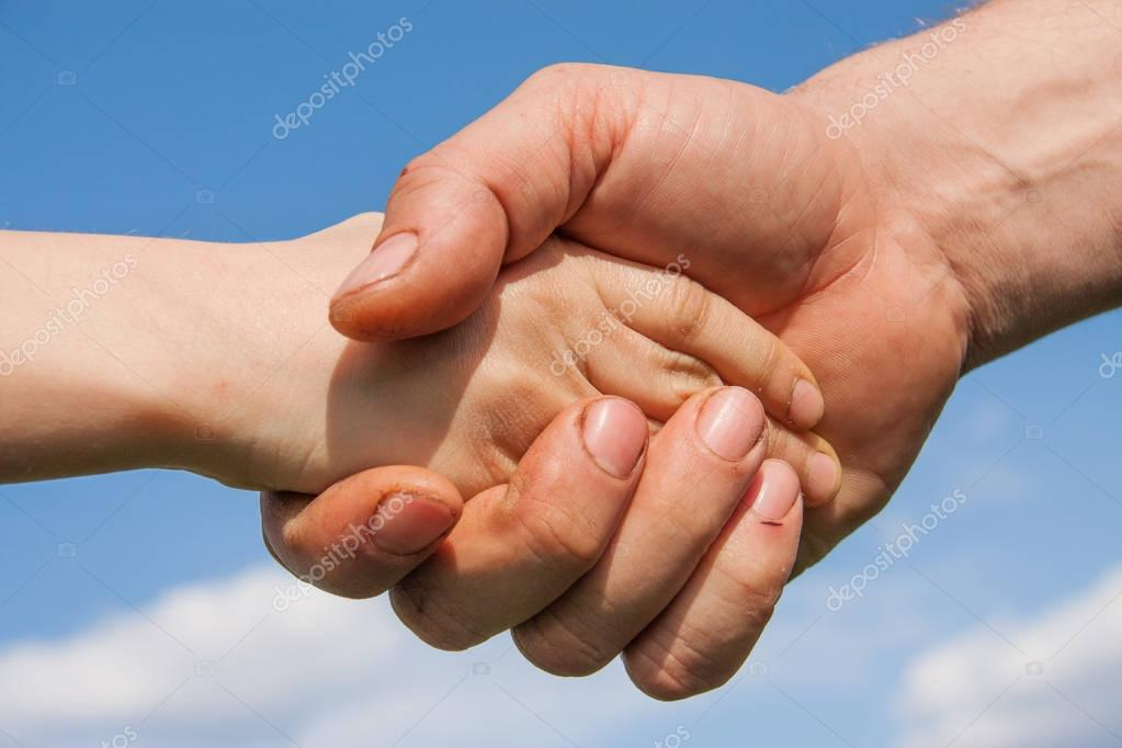 Handshake of a child and an adult against a blue sky