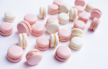 Tender pink and white macarons on white background. Natural light. Selective focus