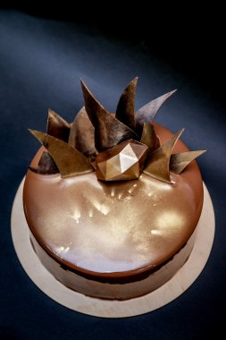 Trendy modern chocolate mousse cake decorated with mirror glaze and chocolate decor. Black background.