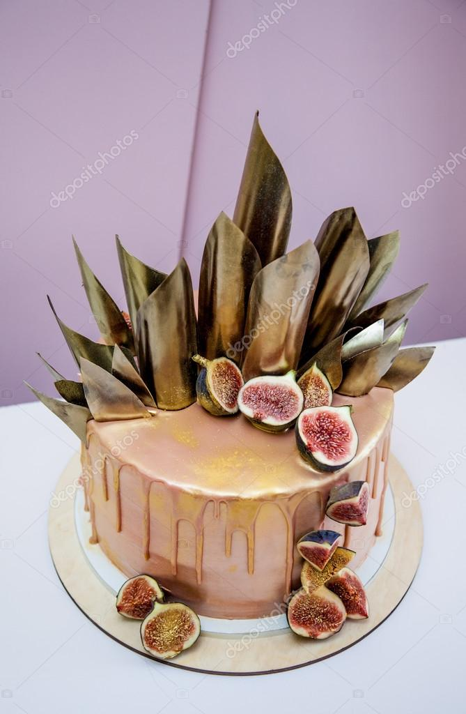 Trendy modern chocolate caramel layered cake decorated with chocolate glaze, figs and chocolate decor.