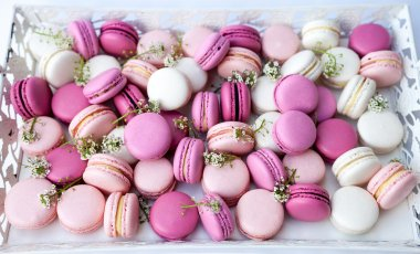 White tray full of colorful macarons shades of pink. Natural light. Selective focus.