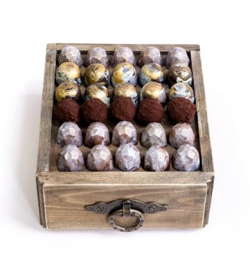 Chocolate hand made painted candy bonbons on a wooden box. Isolated on white. Natural light